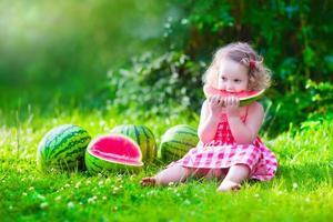 bedårande liten flicka som äter vattenmelon foto