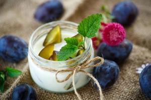 söt mjölk yoghurt med färska plommon foto