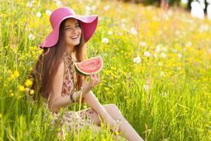 ung vacker kvinna som äter en vattenmelon