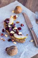 smörgås med grönsaker, nötter och ett päron på rågbröd foto