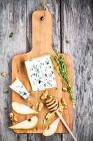 blå ost med skivor av päron, nötter och honung foto