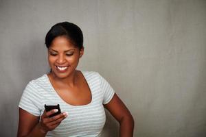 leende flicka smsar på sin mobiltelefon foto