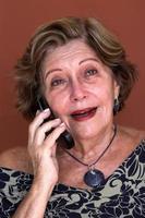 äldre kvinna pratar i mobiltelefonen foto