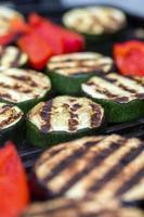 zucchini aubergine och röd paprika på en grill foto