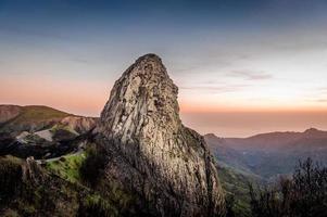 hög sten vid solnedgången foto