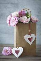 romantisk gåva med rosor och hjärtan foto