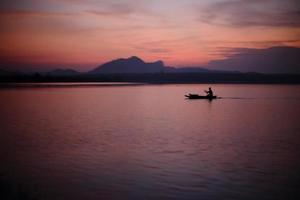 floden och silhuetten fiskare foto
