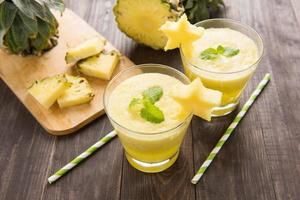 ananassmoothie med färsk ananas på träbord foto