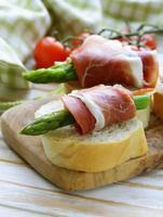 delikatessförrätt grön sparris och rökt skinka foto