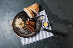 4 rostade nuremberger bratwurste / korvar med surkål, sett ovanifrån.