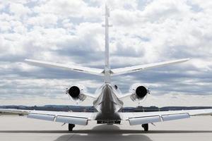 flygplan learjet plan framför flygplatsen med molnig himmel