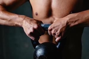närbild av atletiska händer som lyfter en kettlebell foto