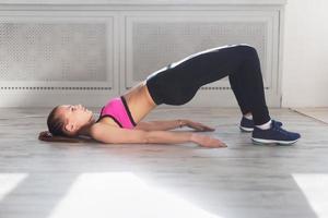 sidovy av ung kvinna som gör gymnastik halvbron foto