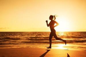 kvinna springer vid solnedgången foto