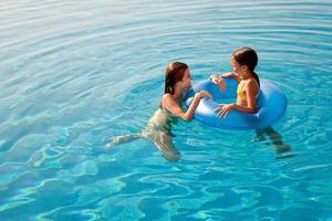 flickor med i uppblåsbar ring i poolen foto
