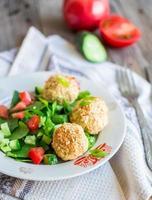 bakade kikärter bollar med sesam- och grönsakssallad, selektiv fokus foto