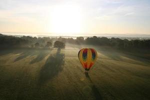 solnedgång över fält och varmluftsballong foto