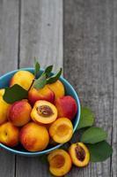 färska persikor i blå skål foto