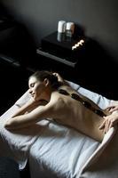 ung kvinna med en varm stenmassageterapi foto