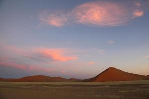 puffiga rosa moln över röda sanddyner foto