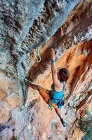bergsklättrare som klättrar upp en klippa foto
