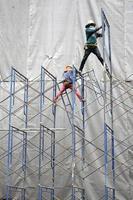 byggarbetsarbetare på byggnadsställningar. foto