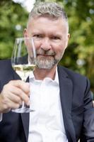 man med ett glas vin foto