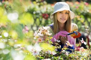 kvinnlig blomsterhandlare i trädgården foto