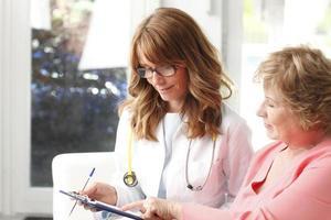 kvinnlig läkare med äldre patient foto