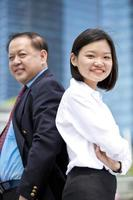 asiatisk affärsman och ung kvinnlig stående foto
