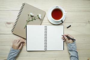 kvinnliga händer skriver på en öppnad anteckningsbok foto