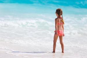 bedårande liten flicka på stranden foto