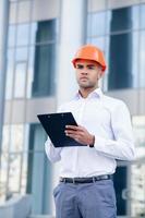 attraktiv ingenjör arbetar med byggnadsplanen foto