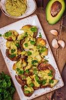 bakade potatis serveras med guacamole foto