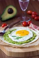 frukost med stekt ägg och sås av avokado på grillad