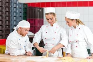 lärling i bageri som gör kringlor och skeptiska bagare som tittar på foto