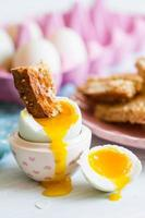 öppnade kokt blåtandägg med mjuk äggula med rostat bröd foto