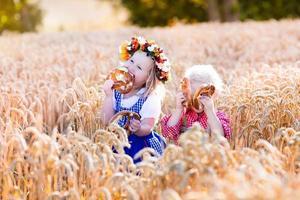 barn i bayerska dräkter i vetefält foto
