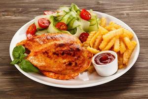 grillade kycklingfiléer, pommes frites och grönsaker på vit bakgrund