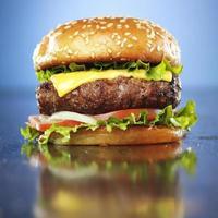 hamburgare med smält ost och sesambulle foto