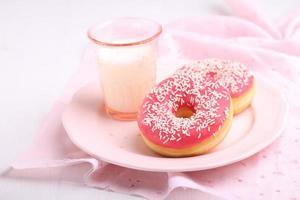 söt munk med rosa glasyr och mjölk foto