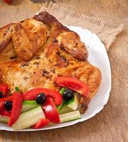liten grillad kyckling med grönsaker på en vit skål foto