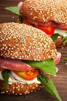 hamburgare med bacon, ruccola och tomat på rustik träbakgrund foto