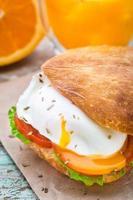 hamburgare med pouched ägg och tomat foto