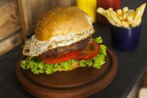 hamburgare med pommes frites på träbord foto