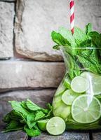 vatten med limefrukter och mynta på träbakgrund foto