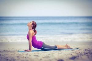 brunett gör yoga på träningsmatta foto