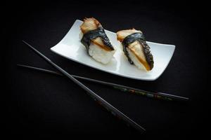 två nigiri ålsushi och ätpinnar på svart foto
