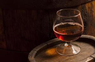 glas konjak i källaren med gamla fat foto