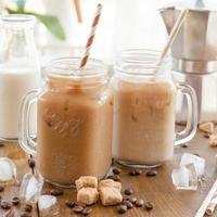 två iskaffe i en vintage burk med sugrör